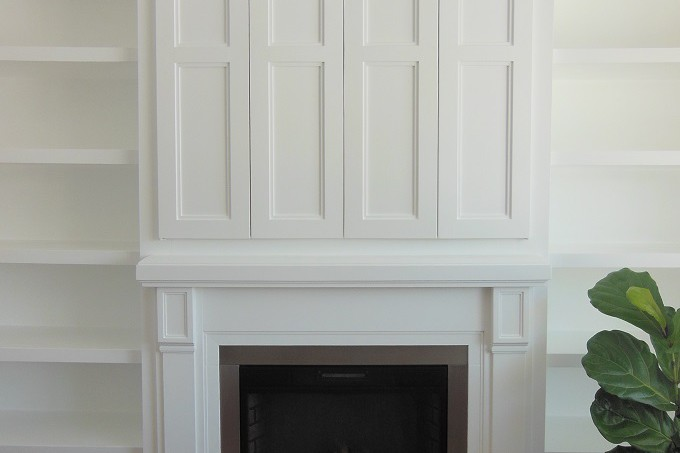 fireplace with doors above for tv